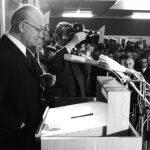 """Am 25. Oktober 1971 ist es dann soweit: die Gesamthochschule Kassel (GhK) wird eröffnet. Es ist eine Gründungsfeier in """"unkonventioneller Atmosphäre ohne akademische Talarfeierlichkeit"""", wie die Hessische Allgemeine schreibt. In der vollbesetzten Mensa am AVZ hält Kassels Oberbürgermeister Karl Branner seine Eröffnungsrede (Foto). Er lobt die GhK als """"zukunftsweisende Bildungsstätte"""", die beispielhaft für die Bundesrepublik Deutschland sei. Auch vom hessischen Ministerpräsidenten Albert Osswald gibt es Lob: Das """"Kasseler Modell"""" sei richtungsweisend für Hochschulreformen sowohl in Hessen als auch in der Bundesrepublik. Noch nie sei eine Hochschule in so kurzer Zeit errichtet worden. Beide betonen, dass schon viel erreicht, aber noch viel zu tun sei. Am nächsten Tag startet der Lehrbetrieb der GhK mit 2.913 Studierenden."""