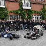 """Mit dem Herkules Racing Team ist die Uni Kassel auch im Motorsport sehr erfolgreich. Seit 2009 planen, konstruieren und fertigen Studierende aus verschiedenen Fachbereichen eigenverantwortlich einen Formelrennwagen für die Formula Student, einen internationalen Konstruktions- und Designwettbewerb. Dabei gewinnt nicht unbedingt der flotteste Bolide, sondern auch Konstruktion, Rennperformance, Finanz- und Marketingplanung sowie Ingenieursleistung zählen zur Gesamtwertung. Bei der ersten Teilnahme 2011 auf dem Hockenheimring holt das Team die Auszeichnung """"Best Newcomer"""" und fährt in den nächsten Jahren weitere Erfolge ein. In der bisher erfolgreichsten Saison 2017 schafft man in Italien den Sprung aufs Treppchen und kann bei Wettbewerben in Deutschland und Österreich Top-Ten-Platzierungen holen. Seit 2018 baut das Team einen Boliden mit Elektroantrieb – hier das Roll-Out 2018 mit """"Hades"""" (Verbrenner) und """"Zeus"""" (E-Auto) – und entwickelt seit 2020 ein Driverless-Konzept zum autonomen Fahren."""